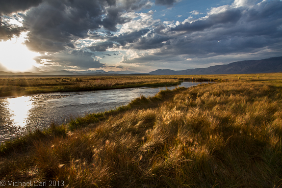 The Owens River flows through a flat high desert valley of grasses and sagebrush.